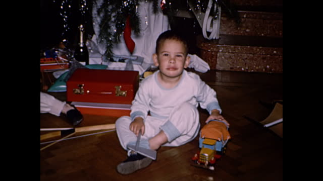 1960s boys with christmas stocking, presents and tree - home movie - stockings stock videos & royalty-free footage