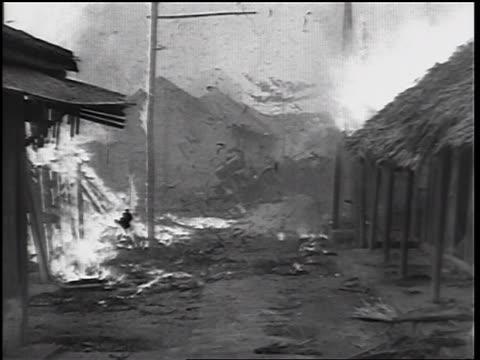 b/w 1960s burning huts in village / vietnam war / newsreel - 掘建て小屋点の映像素材/bロール