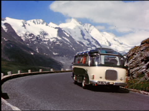 1960s buses, Volkswagen bugs + couple on motorcycle driving around curve in Alpine road
