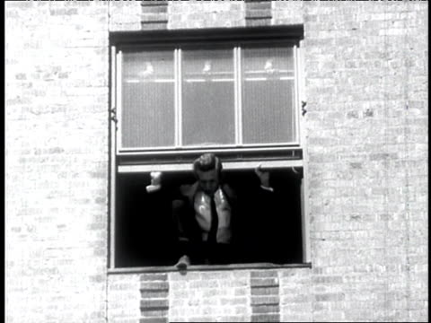 1960s B/W Man climbs out of window, looks down at city street, fingers slipping from window