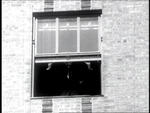1960s b/w man walks down hallway, opens window and looks out onto city street - open window stock videos and b-roll footage