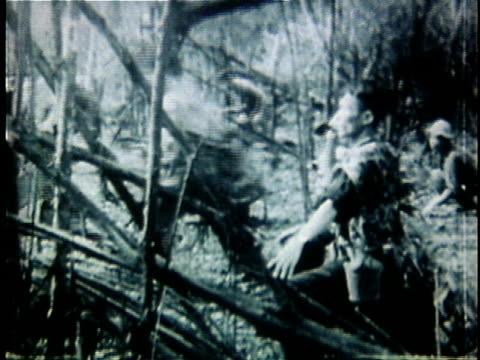 1960s b/w montage viet cong soldiers advancing through jungle during vietnam war / vietnam - ベトコン点の映像素材/bロール