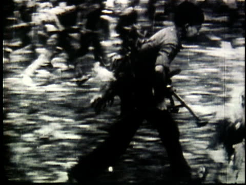 1960s b/w montage viet cong soldiers advancing through jungle lying down and firing / vietnam - ベトコン点の映像素材/bロール