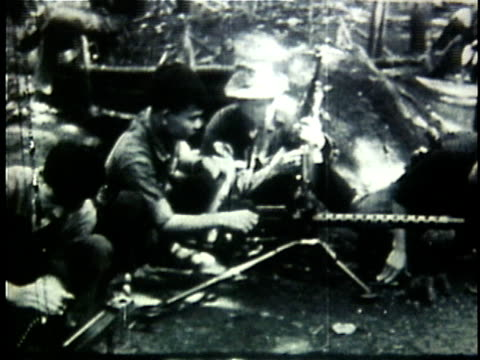 1960s b/w montage viet cong soldiers cleanng their guns at jungle camp during the vietnam war / north vietnam - north vietnam stock videos & royalty-free footage