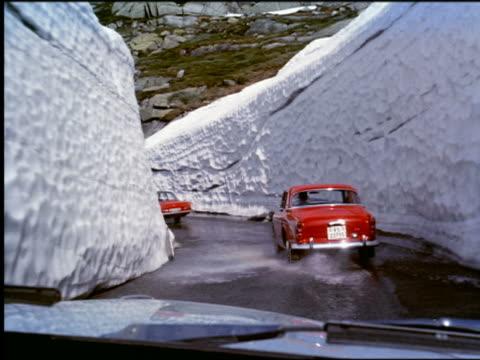 vídeos de stock, filmes e b-roll de 1960s car point of view behind cars + bus on winding mountain road lined with snow + ice / switzerland - ponto de vista de motorista