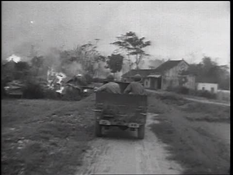 b/w 1960s car point of view behind soldiers in truck driving thru burning village / vietnam war / newsreel - burning stock-videos und b-roll-filmmaterial