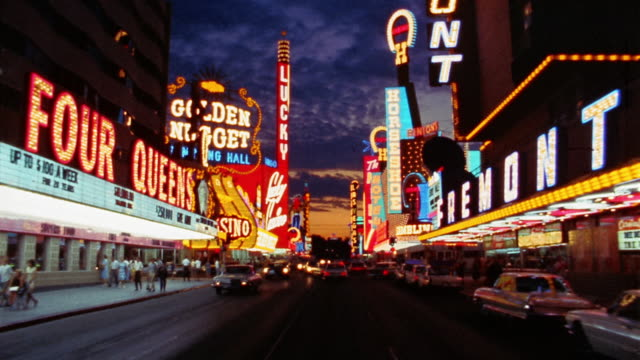 stockvideo's en b-roll-footage met 1960s car point of view driving down las vegas strip at night with clouds in sky / las vegas, nevada - gokken