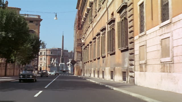 1960s car point of view driving on rome city street towards the monte cavallo monument and going around turn - monumento video stock e b–roll