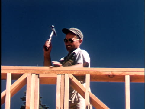 stockvideo's en b-roll-footage met ms la 1960s carpenter hammering nails into wood frame of house, clear sky in background, california / usa - prelinger archief