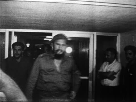 b/w 1960s che guevara fidel castro exiting building thru crowd / newsreel - che guevara stock videos & royalty-free footage