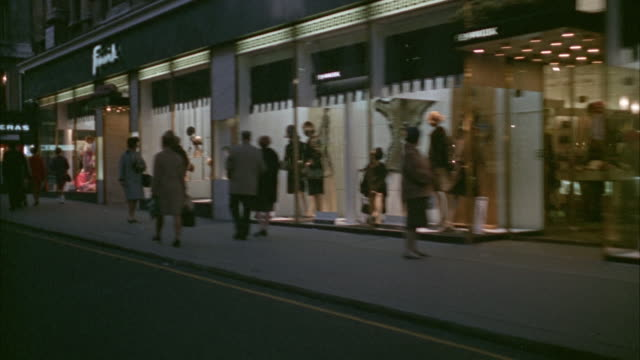1960s ws pov city streets with shoppers outside stores / london, uk - england stock videos & royalty-free footage