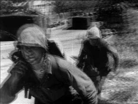 b/w 1960s close up 2 us marines running past camera on street during revolution / dominican republic - イスパニョーラ点の映像素材/bロール