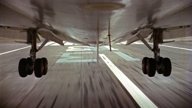 1960s close up belly of plane flying over houses and landing  / taking off again / landing gear closing - landing touching down stock videos & royalty-free footage