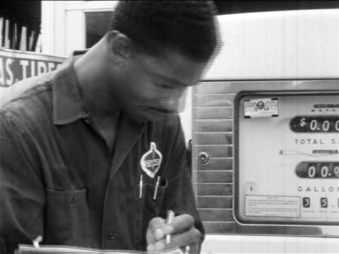 b/w 1960s close up black service station attendant checking gas pump + writing on clipboard / doc. - gas station attendant stock videos and b-roll footage
