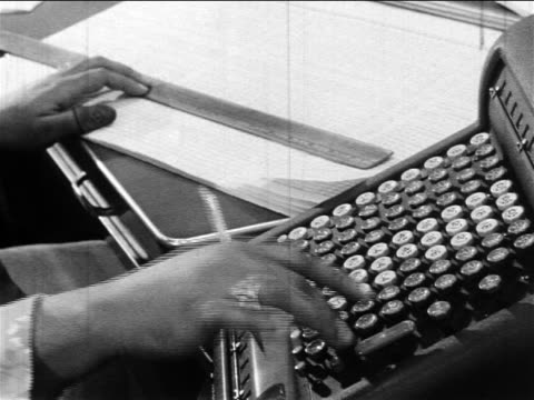 b/w 1960s close up black woman's hands typing quickly on adding machine while holding ruler on document - 電卓点の映像素材/bロール