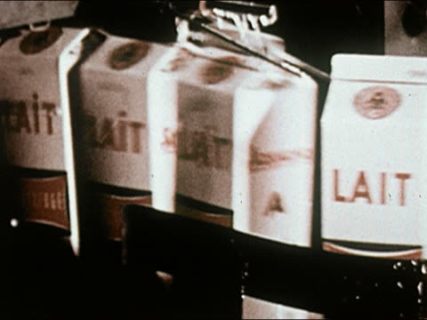vídeos de stock e filmes b-roll de 1960s close up cartons of milk labeled lait being rinsed off on conveyor belt - leite