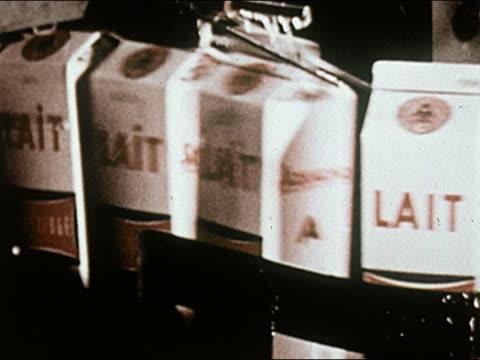 vídeos y material grabado en eventos de stock de 1960s close up cartons of milk labeled lait being rinsed off on conveyor belt - leche
