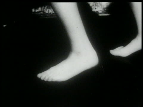 B/W 1960s close up feet of woman in stockings doing the Twist