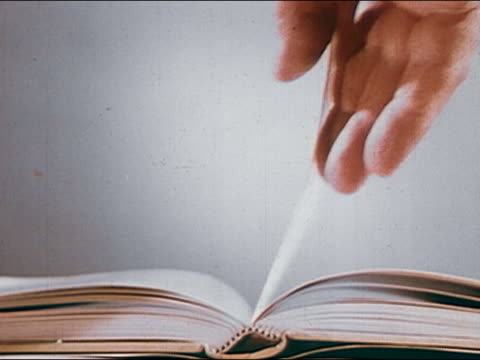 1960s close up hand turning page of book