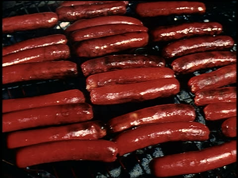 1960s close up hand using tongs to pick up hot dog from grill - hot dog stock videos & royalty-free footage