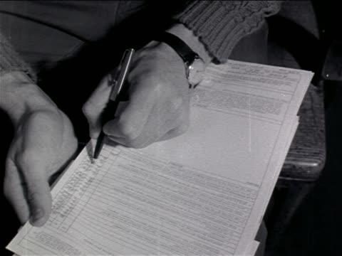vídeos y material grabado en eventos de stock de 1960s close up man's hand writing on enlistment form / vietnam war / newsreel - a la izquierda de