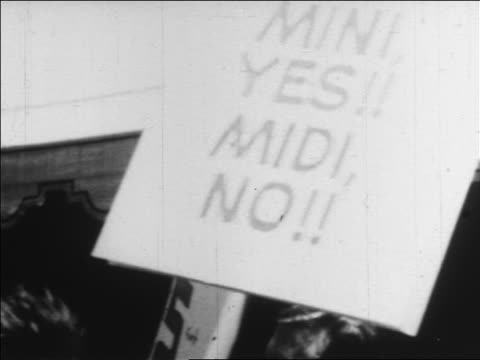 b/w 1960s close up people carrying posters in demonstration for minis / newsreel - mini skirt stock videos & royalty-free footage