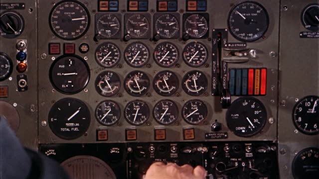 1960s close up pilots' hands on control panel in cockpit of airplane