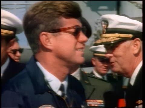1960s close up profile john kennedy in sunglasses on ship with naval officers in background / newsreel - john f. kennedy myndighetsroll bildbanksvideor och videomaterial från bakom kulisserna