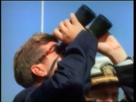 1960s close up profile john kennedy looking up with binoculars watching missile / newsreel - john f. kennedy myndighetsroll bildbanksvideor och videomaterial från bakom kulisserna