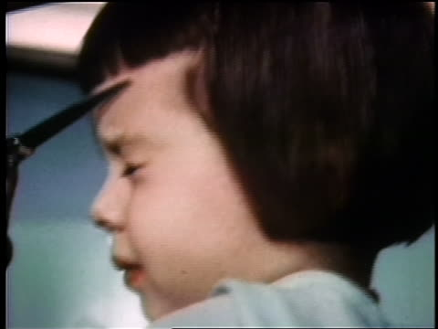 1960s close up profile scissors cutting bangs on flinching young girl / industrial - bangs stock videos & royalty-free footage