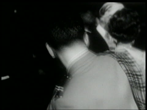 B/W 1960s close up REAR VIEW of man in Scottish uniform dancing the Twist with woman at formal party