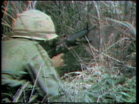 1960s close up rear view us soldier lying in grass shooting rifle during vietnam war - 歩兵点の映像素材/bロール