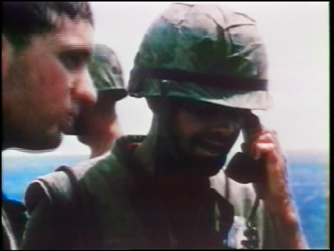 1960s close up soldier in helmet talking on telephone outdoors / other soldiers around him / vietnam war - other stock videos & royalty-free footage
