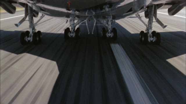 1960s close up wheels of 747 jet plane during take off / landing gear being raised in flight