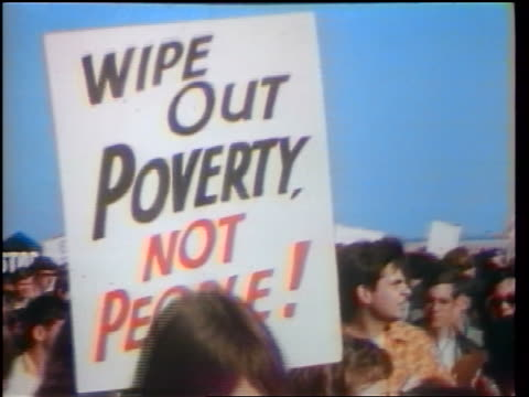 1960s close up wipe out poverty not people poster being carried in peace demonstration / washington dc - peace demonstration stock videos and b-roll footage