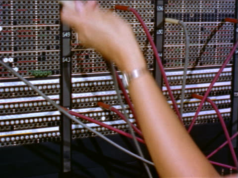vídeos de stock, filmes e b-roll de 1960s close up woman's hand unplugging cable from telephone switchboard / educational - estilo retrô