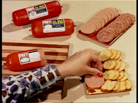 1960s close up woman's hands slicing baloney loaf + putting it on tray with crackers + salami - yorkville illinois stock videos & royalty-free footage