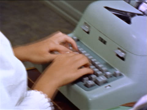 1960s close up woman's hands typing on typewriter / tilt up to her face in eyeglasses looking down / educ.