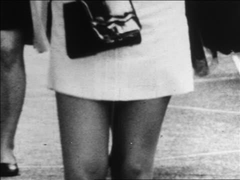 b/w 1960s close up woman's legs in mini skirt walking on sidewalk / carrying purse / newsreel - minigonna video stock e b–roll