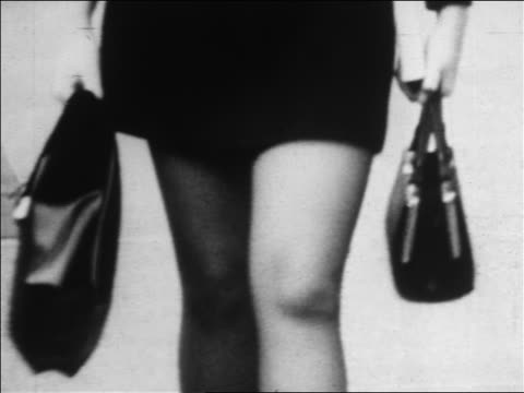 b/w 1960s close up woman's legs in mini-skirt walking toward camera / carrying purse / newsreel - skirt stock videos & royalty-free footage