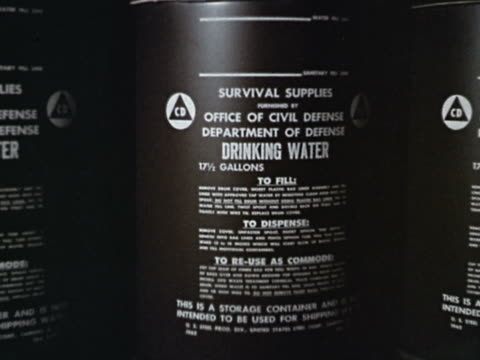 1960s close up writing on barrels of drinking water furnished by the office of civil defense - pianificazione di emergenza video stock e b–roll