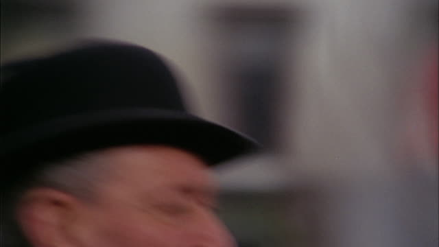 1960s close up zoom out man in bowler hat walking w/umbrella / pan to nelson's column / trafalgar square /london - hat stock videos & royalty-free footage