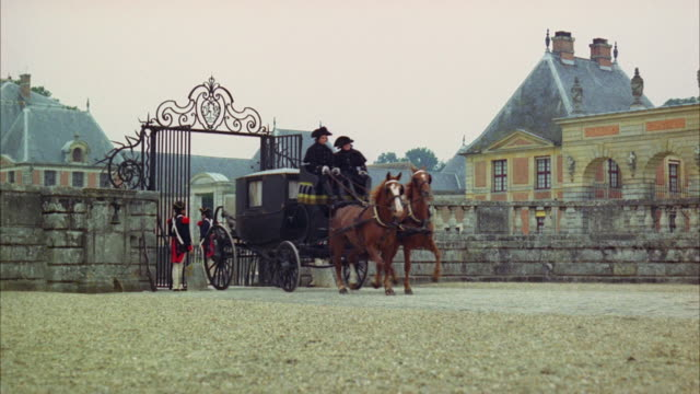 1960s ws coach with two people aboard going through gate guarded by soldiers - 1960 1969 stock-videos und b-roll-filmmaterial