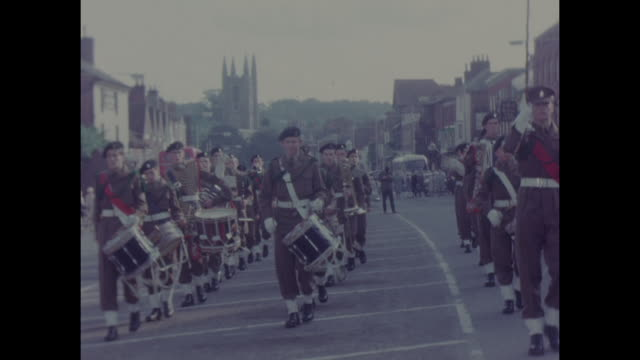 1960s colour home movie footage of an English cadet marching band on parade through a town