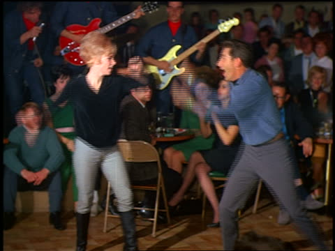 vídeos de stock, filmes e b-roll de 1960s couple dancing the watusi indoors with musicians + crowd watching in background - 1960
