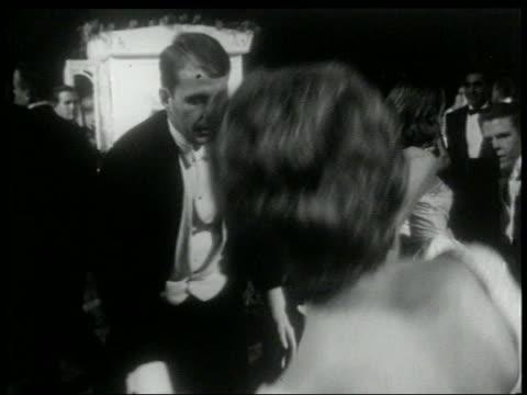 B/W 1960s couple in formalwear doing the Twist on dance floor