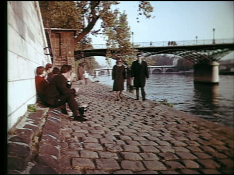 1960s couple walk on cobblestone bank of seine river past people sitting / pont sully in background / paris - river seine stock videos & royalty-free footage