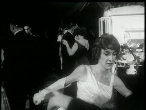 B/W 1960s couples in formalwear dancing the Twist on dance floor