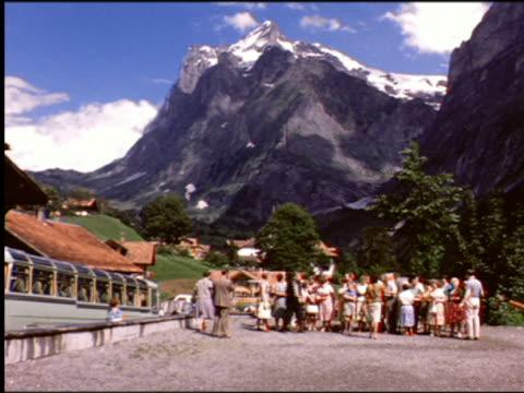 1960s crowd of tourists standing with Alpine village + mountain in background / Grindelwald, Switzerland?