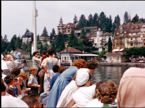 1960s crowded tour boat point of view on Lake Lucerne past approching dock / Tellsplatte, Switzerland